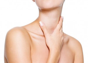 Beautiful woman puts hand on health neck- isolated on white